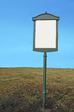 Blank metal signpost. Blank green metal signpost in the grass over blue sky royalty free stock photos