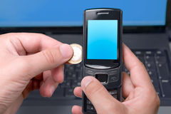 Blank mobile phone charging by coin. Man's hand is holding opened slider cell phone with blank blue screen and pushing coin to charge mobile account Stock Image