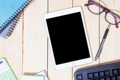 Blank modern digital tablet with papers and pen in the middle of Royalty Free Stock Images