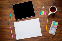 Blank modern digital tablet with papers and pen on a wooden desk. Top view Royalty Free Stock Photos