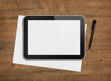Blank digital tablet on a desk. Blank modern digital tablet with papers and pen on a wooden desk. Top view. High quality detailed graphic collage Royalty Free Stock Image