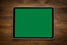 Blank modern digital tablet on a wooden desk. Top. View. With isolated screen Stock Images