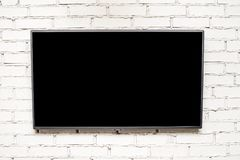 Blank modern flat screen TV at the light brick wall with copyspace for your text, plasma TV royalty free stock images