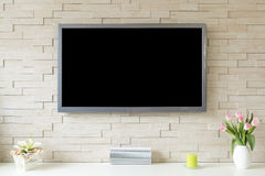 Blank modern flat screen TV at the white brick wall with copy space.  Stock Image