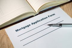 Mortgage applications form and pen on bright wooden office desk. Blank mortgage applications form and pen on bright wooden office desk stock photo