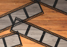 Blank movie film strip. Blank movie or photography film strip lying on the wooden desk Royalty Free Stock Photo