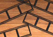 Blank movie film strip. Blank movie or photography film strip lying on the wooden desk Stock Images