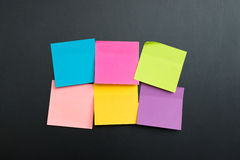 Blank multi color sticky notes. Blank multi colors sticky notes arranged in two rows on black board Royalty Free Stock Photography