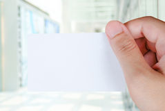Blank name card in hand over blur office background Royalty Free Stock Image