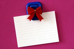 Blank Note. Blank white note paper hanging from magnetic pinup with red bow on pink background Royalty Free Stock Photos