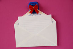 Blank Note. Blank white note paper in white envelope hanging from magnetic pinup with red bow on pink background Royalty Free Stock Photo