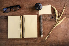 Blank note book with eye glasses on old wooden desk Stock Image