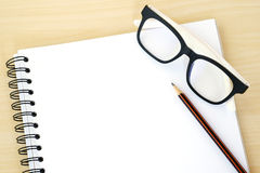 Blank note book, eye glasses and pencil on wood background Stock Images