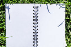 Blank Note Book in Fresh Green Grass Background Royalty Free Stock Images