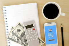 Blank note book, money, calculator and smart phone with pay now Royalty Free Stock Photos
