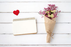 Blank note book paper, fabric heart shape and flower bouquet on Stock Photos