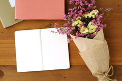 Blank note book paper and flower bouquet on wood background Stock Photos