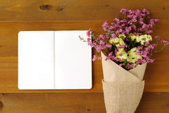 Blank note book paper and flower bouquet on wood background Royalty Free Stock Photos