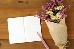 Blank note book paper and flower bouquet on wood background Royalty Free Stock Images