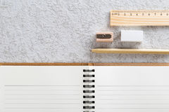 Blank note book with a pen, wooden pencil sharpener , wooden ruler and white eraser. Stock Image