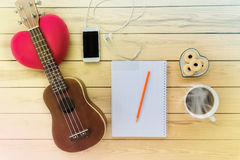 Blank note book and pencil with coffee,cookie, mobile phone and ukulele Stock Image