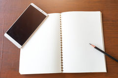 Blank note book with pencil and smartphone on wooden table backg Royalty Free Stock Images