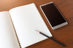 Blank note book with pencil and smartphone on wooden table backg Royalty Free Stock Photos