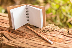 Blank note book. Small  open and pencil on old wooden texture with green nature background. Closeup, Select focus Royalty Free Stock Photography