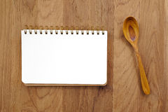 Blank note book and wooden spoon on table Stock Photos