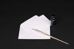 Blank note card with envelope, dip pen and inkwell. Blank note card with envelope, old-fashioned dip pen and inkwell containing blue ink on a black background Royalty Free Stock Photography
