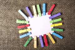 Blank note and color clothespins Stock Photos