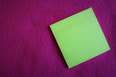 A blank note on fuchsia color background. A yellow blank note on a fuchsia color fabric background royalty free stock image