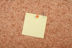Blank note on noticeboard. Blank yellow note pinned to cork noticeboard Stock Photo