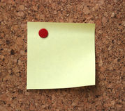Blank note pad. A detail of a blank note pad on cork board Royalty Free Stock Images