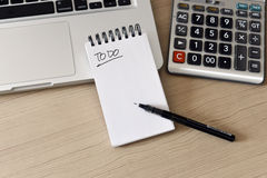 Blank Note Pad, Calculator, Computer, Pen on the Table Royalty Free Stock Images