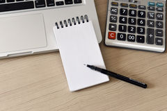 Blank Note Pad, Calculator, Computer, Pen on the Table. Taken in natural light to create realistic indoor mood Royalty Free Stock Photography