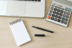 Blank Note Pad, Calculator, Computer, Pen on the Table Royalty Free Stock Photos