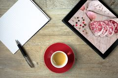 Blank note pad with coffee and tablet computer. With picture of sausage and peppercorns Royalty Free Stock Photos