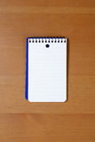 A blank note pad on a desk Royalty Free Stock Image