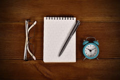 Blank note pad, pen, clock and glasses Royalty Free Stock Images