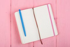 Blank note pad and pen on pink wood. En table Stock Images