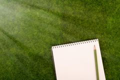Blank note pad and pencil on the grass meadow. Mock up. Blank spiral note pad and pencil on the grass meadow. Mock up Royalty Free Stock Photos