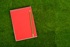 Blank note pad and pencil on the grass meadow. Mock up. Blank spiral note pad and pencil on the grass meadow. Mock up Royalty Free Stock Photo