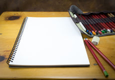 Blank note pad with pencils, folder and eraser on wood table Royalty Free Stock Images