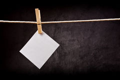 Blank note paper hanging on rope with clothes pins Stock Photos