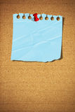 Blank note paper with pin on cork board. Blank blue note paper with push pin on cork board Stock Image
