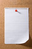 Note paper  Post-It held by a red pushpin. Note paper with a curled up corner on bulletin board ready for your message. With natural shadow Royalty Free Stock Photos