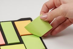 Blank note paper set of different colours forms and sizes. Sticky notes collection on black background. Female hand tear off paper. Note stock photos
