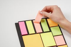 Blank note paper set of different colours forms and sizes. Sticky notes collection on black background. Female hand tear off paper. Note stock images