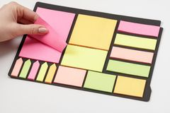 Blank note paper set of different colours forms and sizes. Sticky notes collection on black background. Female hand tear off paper. Note stock photography